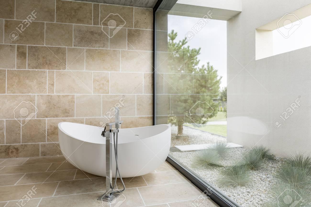 Salle de bains avec fenêtre mur, baignoire et carrelage beige