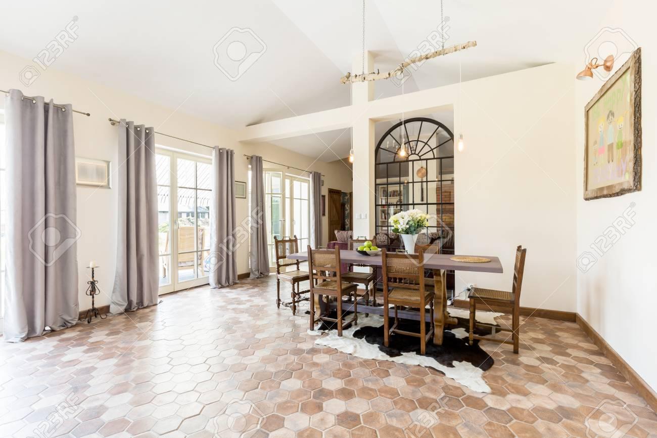 Amplio comedor con mesa y sillas con grandes ventanas y baldosas rústicas