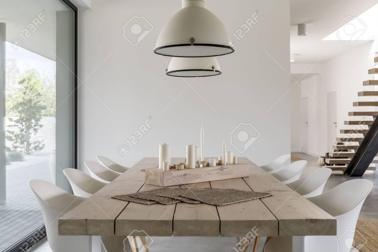 Kamer met houten eettafel witte stoelen en industriële lamp