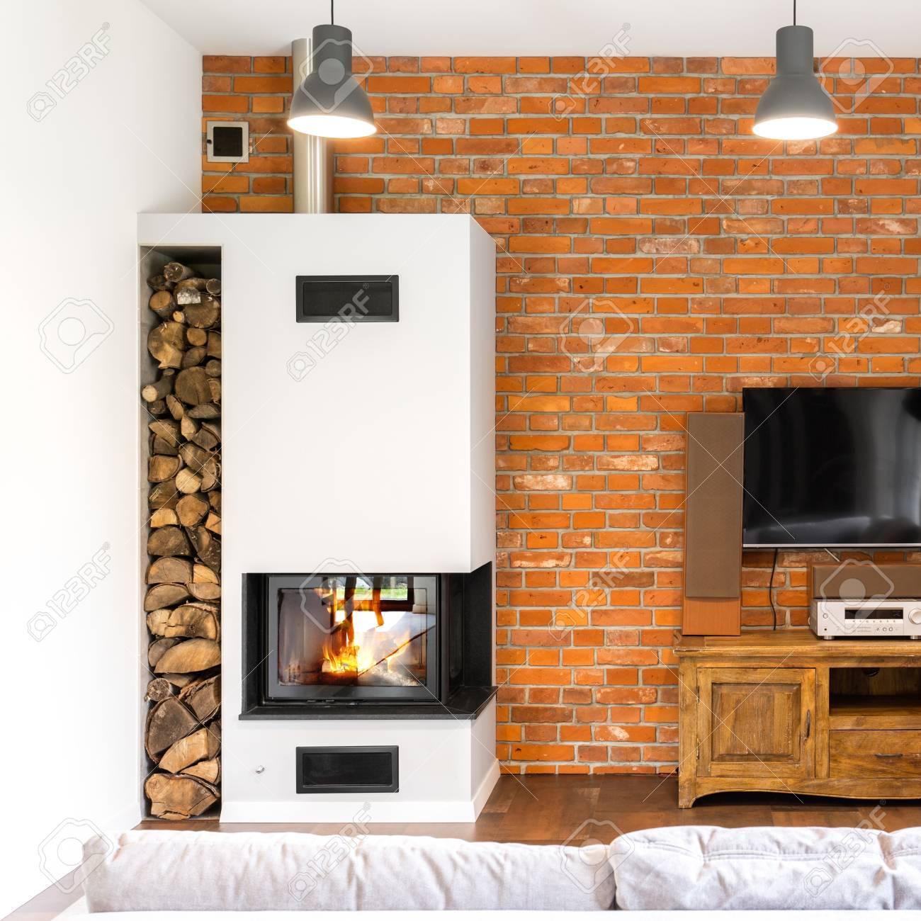 Mur de briques salon avec cheminée moderne, coffret en bois vintage et TV