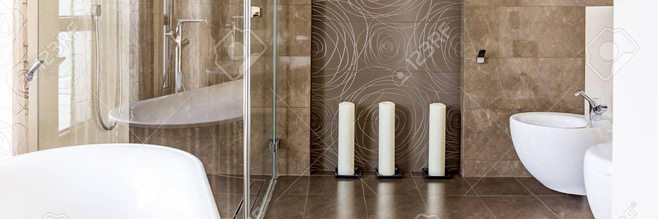 Salle de bain avec carrelage marron, WC et douche à l\'italienne