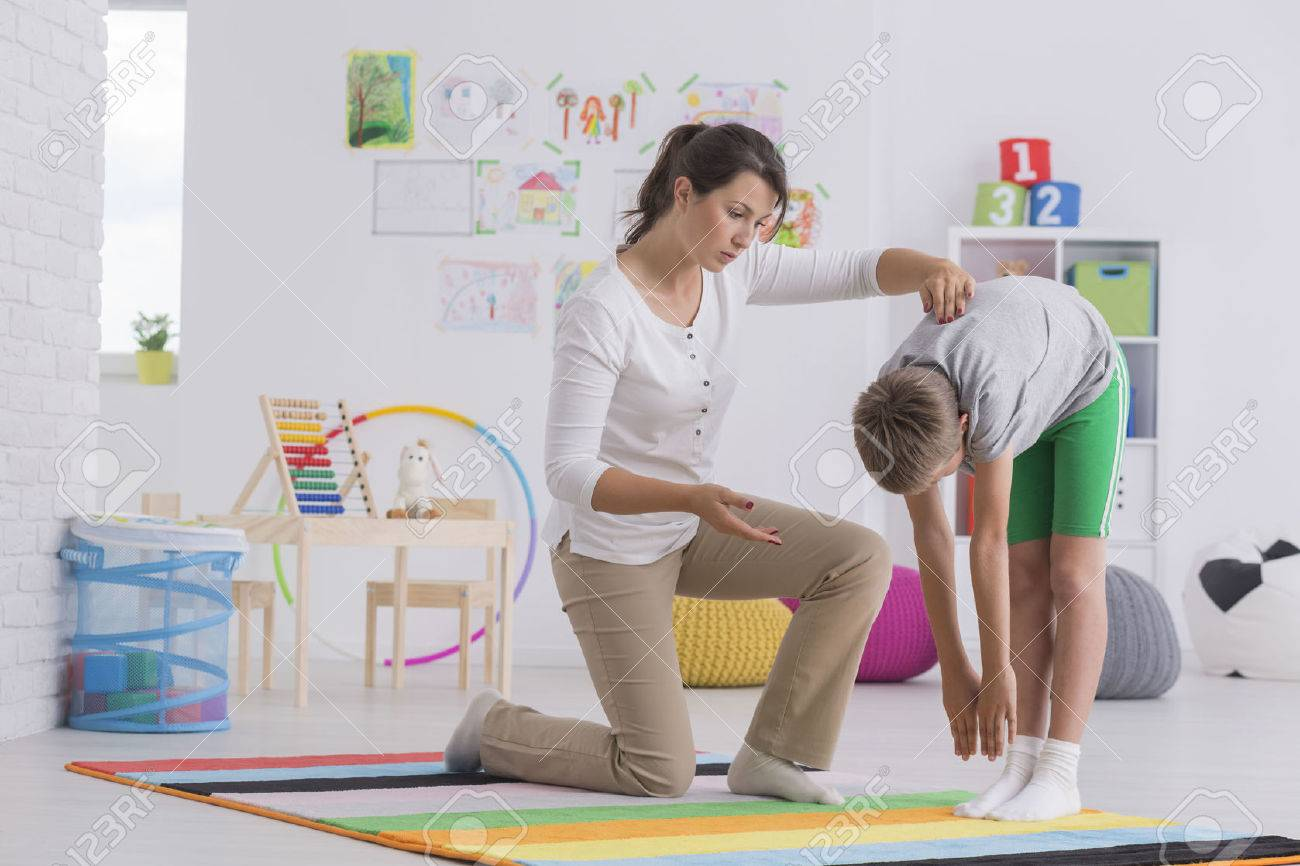 Child standing forward bend while exercising with physiotherapist Standard-Bild - 69988673