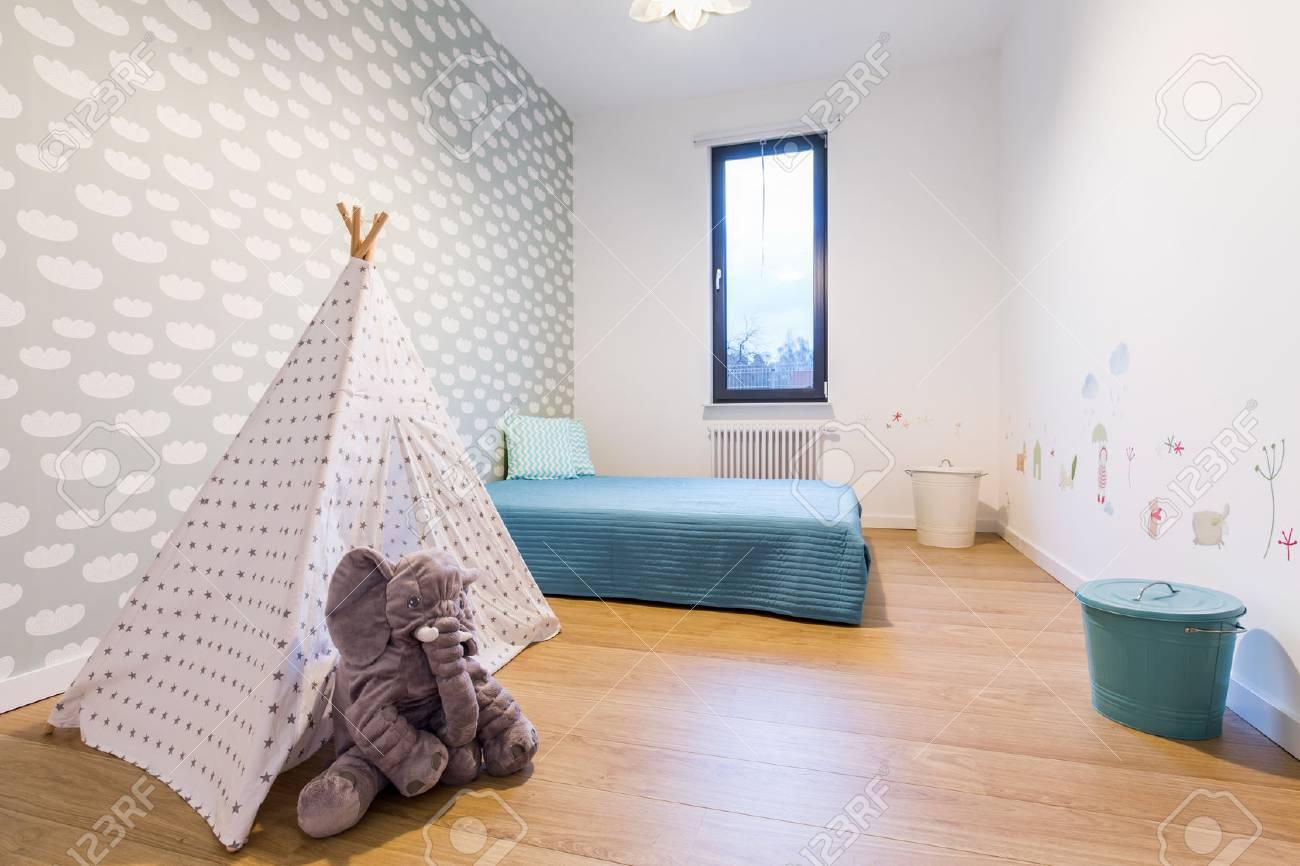 Lit Au Milieu D Une Chambre enfants chambre avec lit bleu par le mur et petite tente tipi au milieu.  sur le fond d'écran de mur avec des images