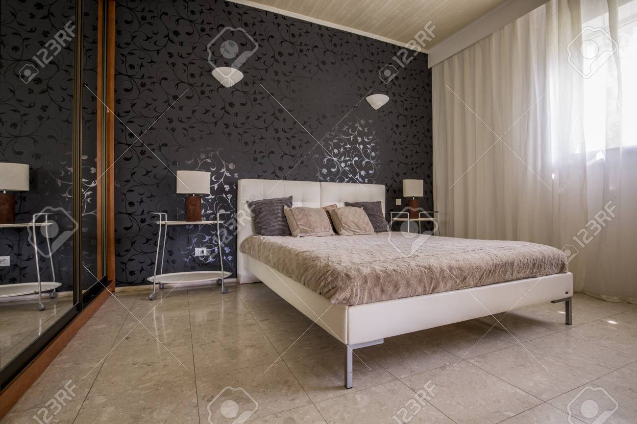 Elegant master bedroom with interesting wallpaper, double bed..
