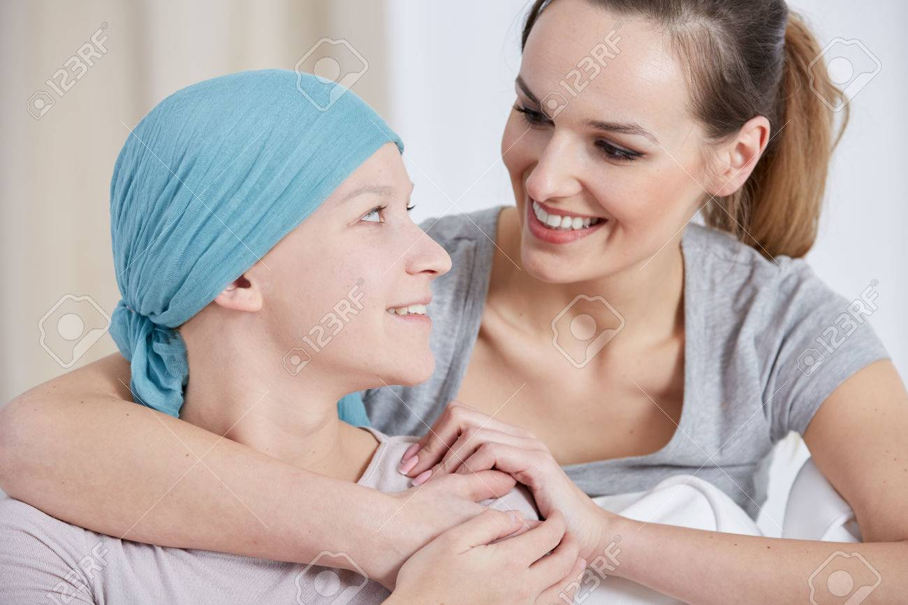 Hopeful cancer woman wearing headscarf, talking with friend Standard-Bild - 70228709