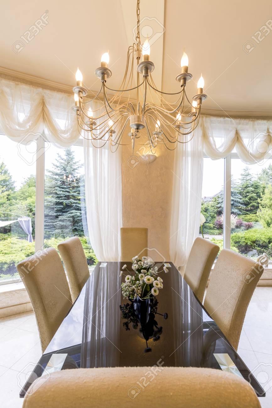Elegante comedor con mesa grande, sillas y araña.