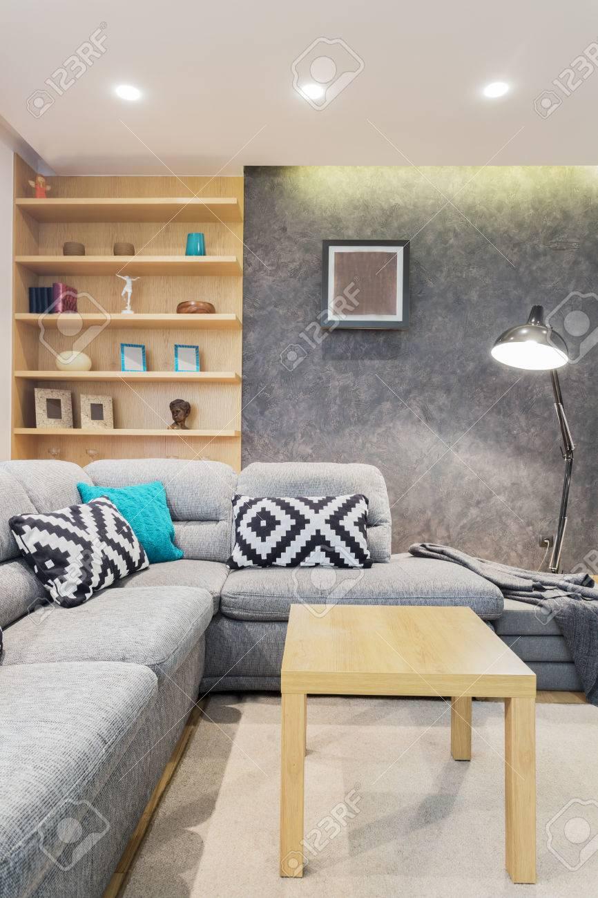 Canapé d\'angle gris avec des coussins à motifs dans un salon de style  scandinave avec des murs en béton
