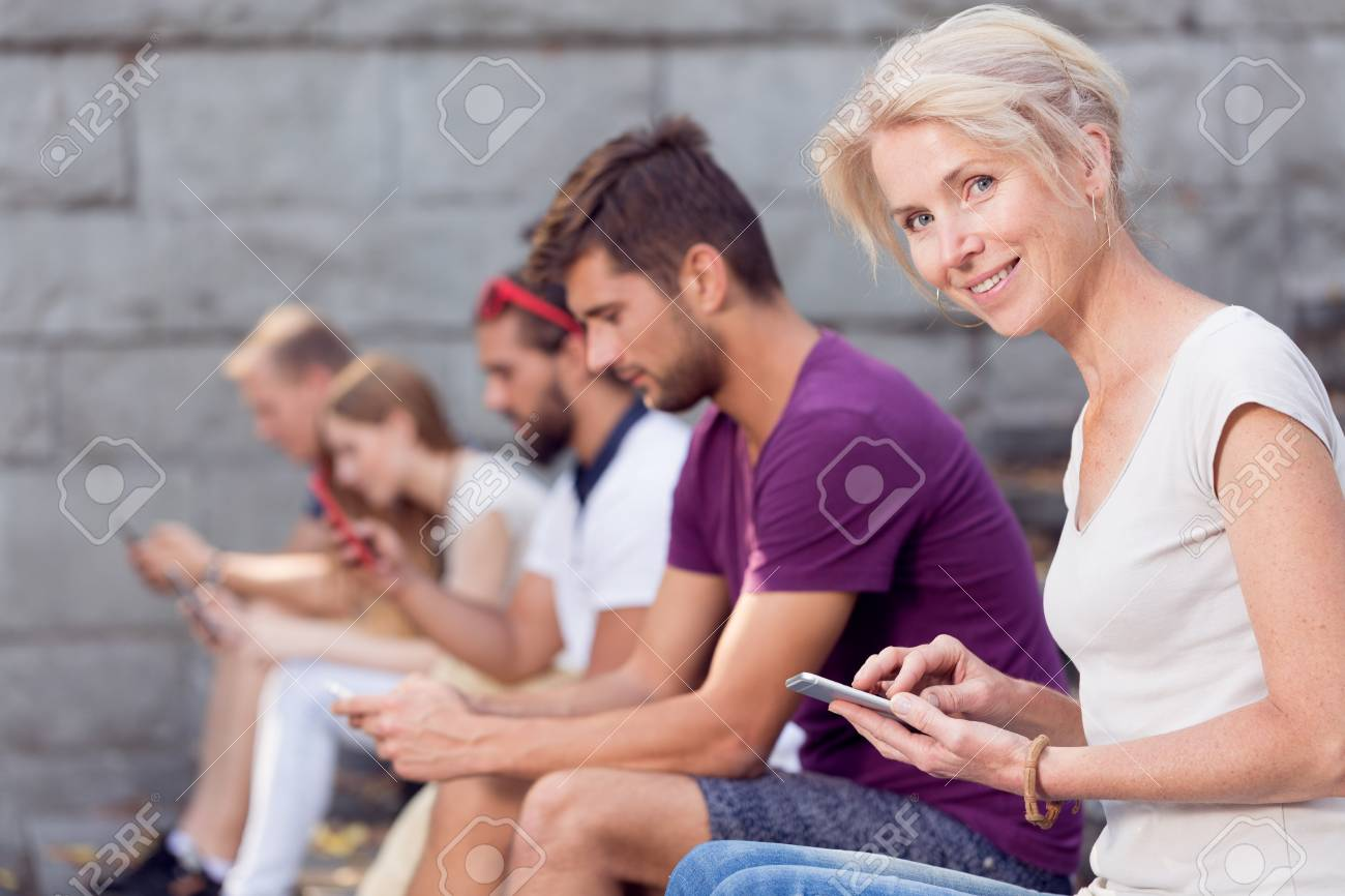Pretty Young Woman With Smartphone Sitting Next To People Texting Friend Stock Photo