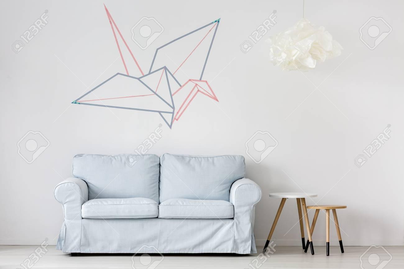 Canapé bleu pastel dans la salle d\'origami de mur blanc