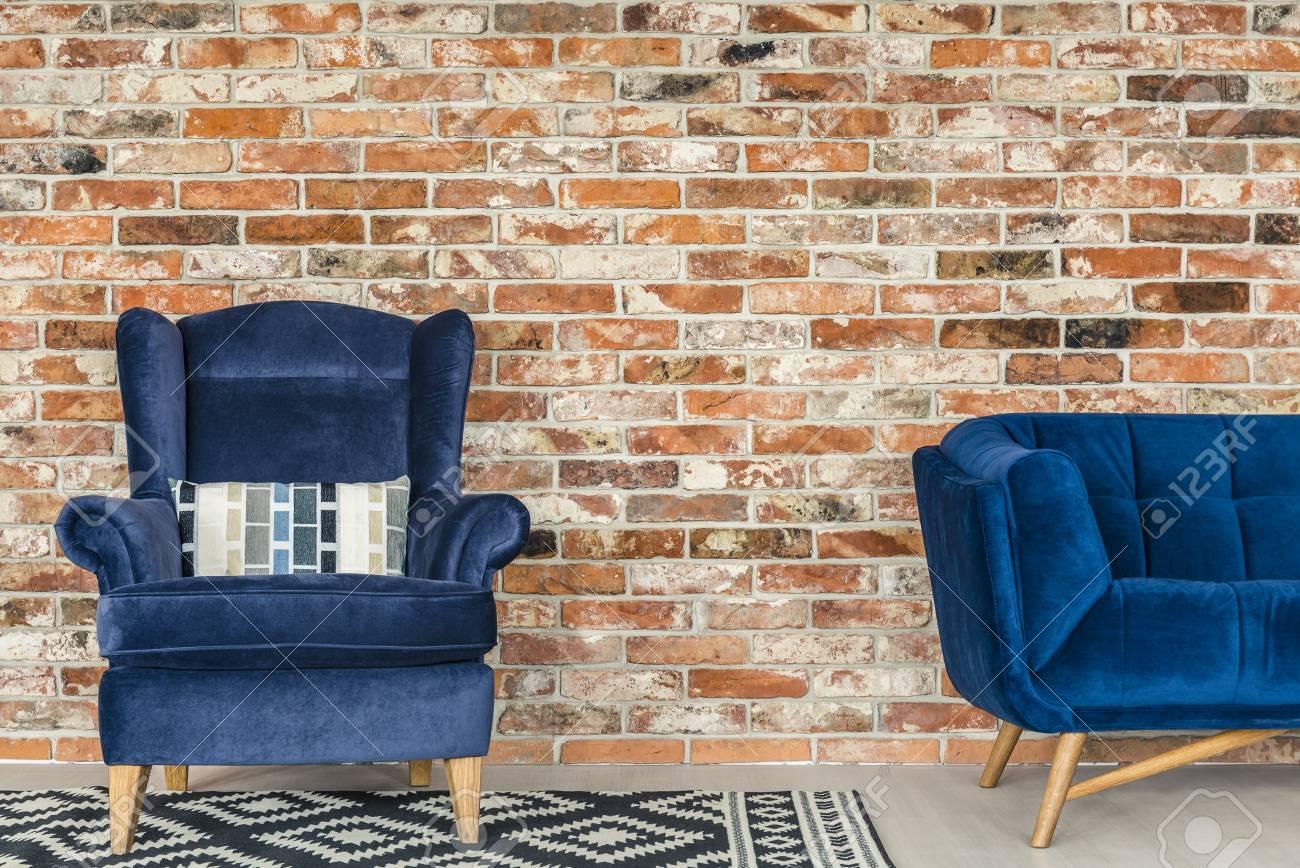 Mur de briques de style industriel, fauteuil bleu, canapé et tapis à motifs