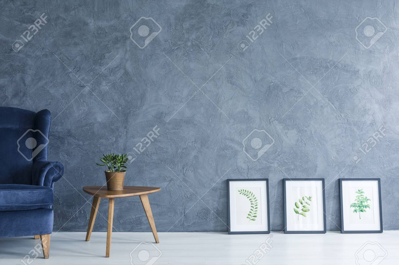 Apartment with blue armchair, side table and leaves paintings - 70237207