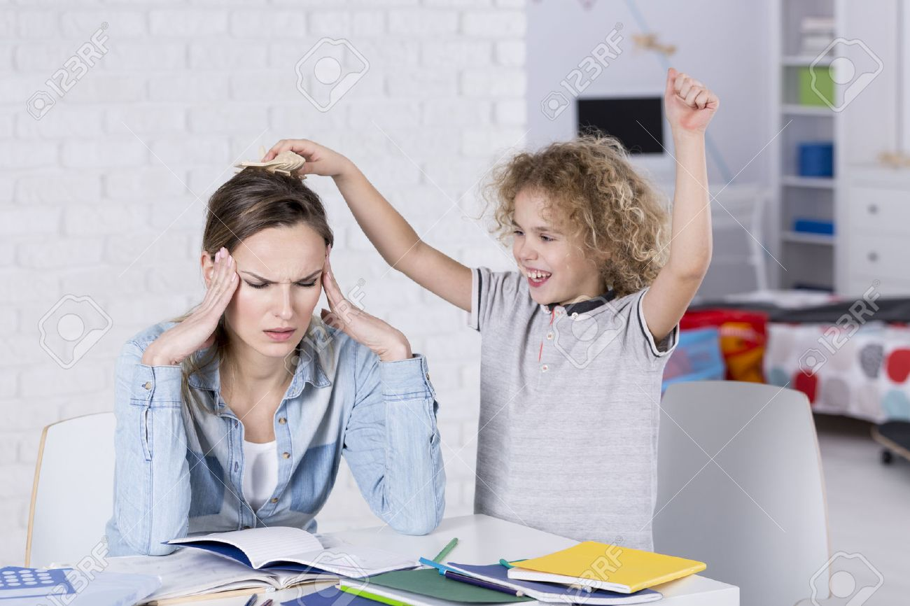 Child annoying his tired mother with headache Stock Photo - 70424540