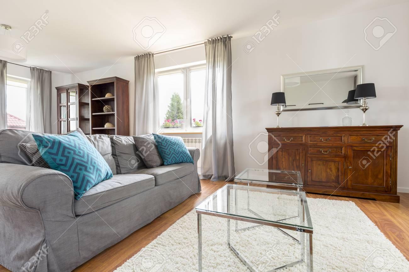 Elegante e luminoso soggiorno con divano, tavolino e comò in legno