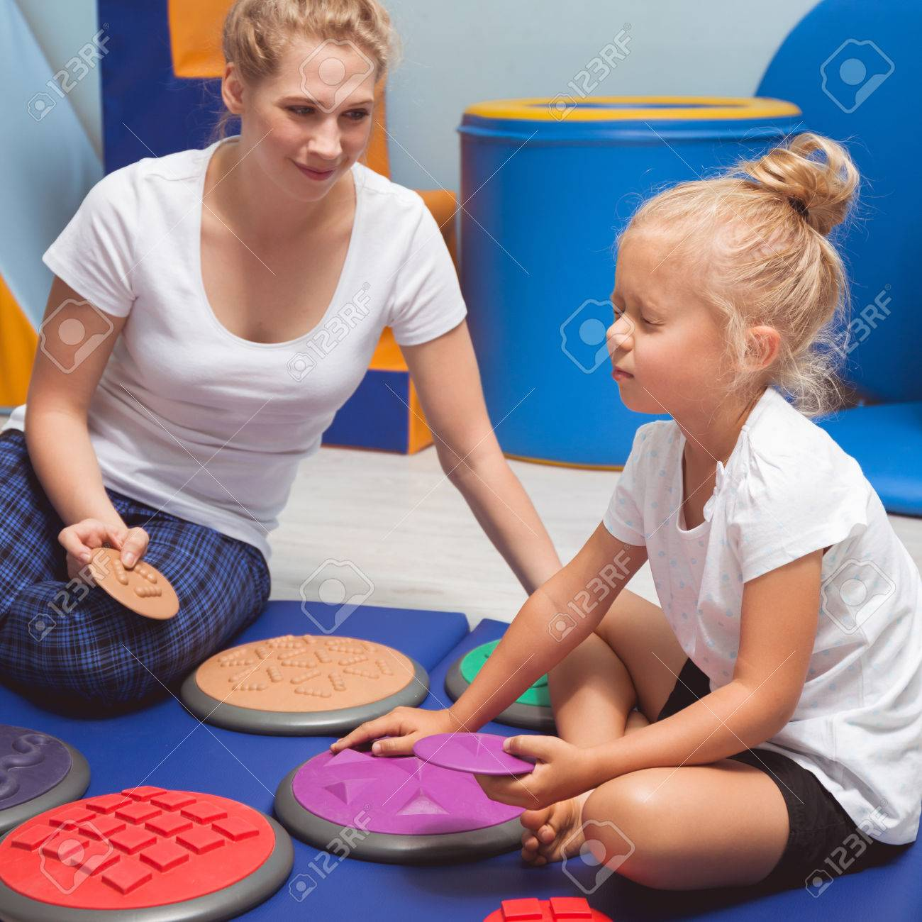 Child touching with closed eyes sensory integration equipment with occupational therapist - 70962721