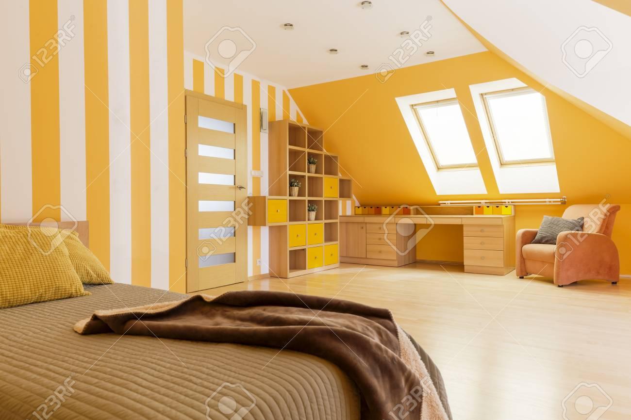 Papier Peint Chambre Mansardée intérieur lumineux de la chambre mansardée avec papier peint à rayures, lit  et espace de travail avec bureau en bois