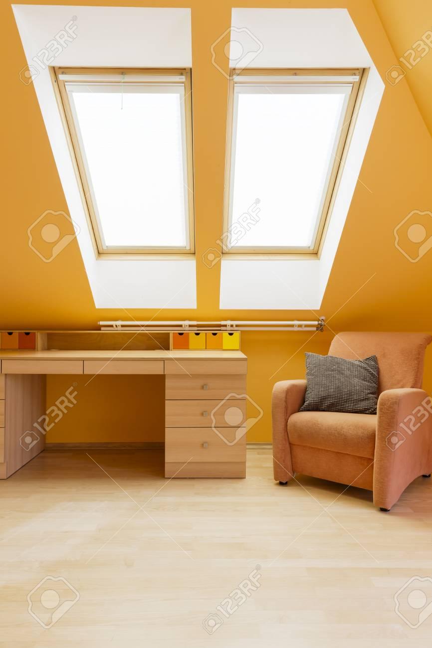 Papier Peint Chambre Mansardée lumineuse chambre mansardée aux couleurs chaudes avec bureau, fauteuil et  fenêtre de toit