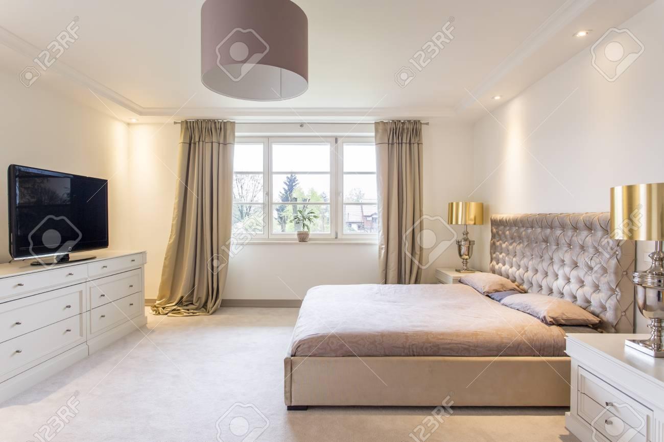 Geräumiges Schlafzimmer Mit Einem Großen Bett, TV Und Goldenen ...