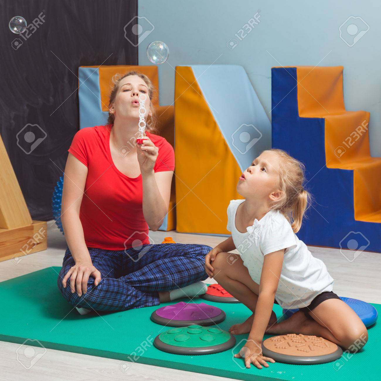 Child and therapist blowing bubbles during sensory integration therapy - 70964065