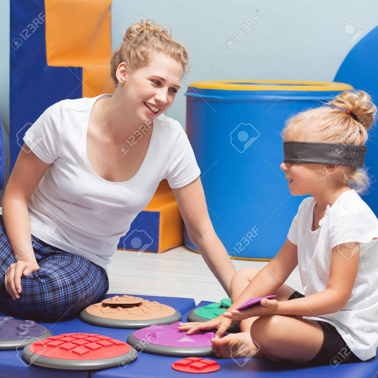 School girl with closed eyes during sensory integration class with therapist - 70964196