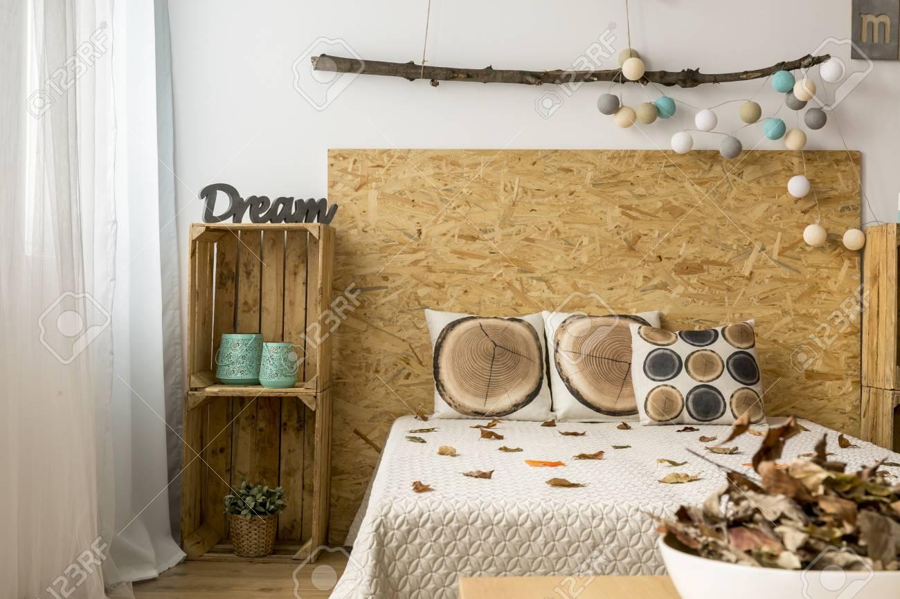 Accogliente camera da letto in tonalità autunnali con letto matrimoniale e  scatole di legno come mobili fai da te