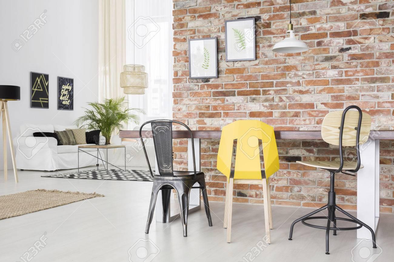 Moderno apartamento con pared de ladrillo, mesa de comedor, silla y sofá