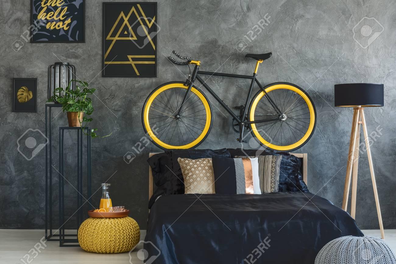 Chambre gris tendance avec lit, vélo et affiches murales