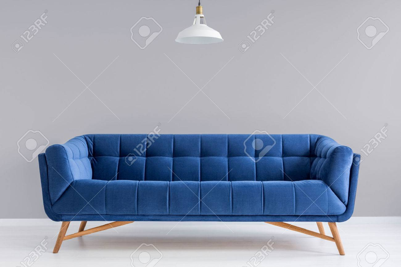 Grey interior with stylish upholstered blue sofa and lamp Standard-Bild - 71340445