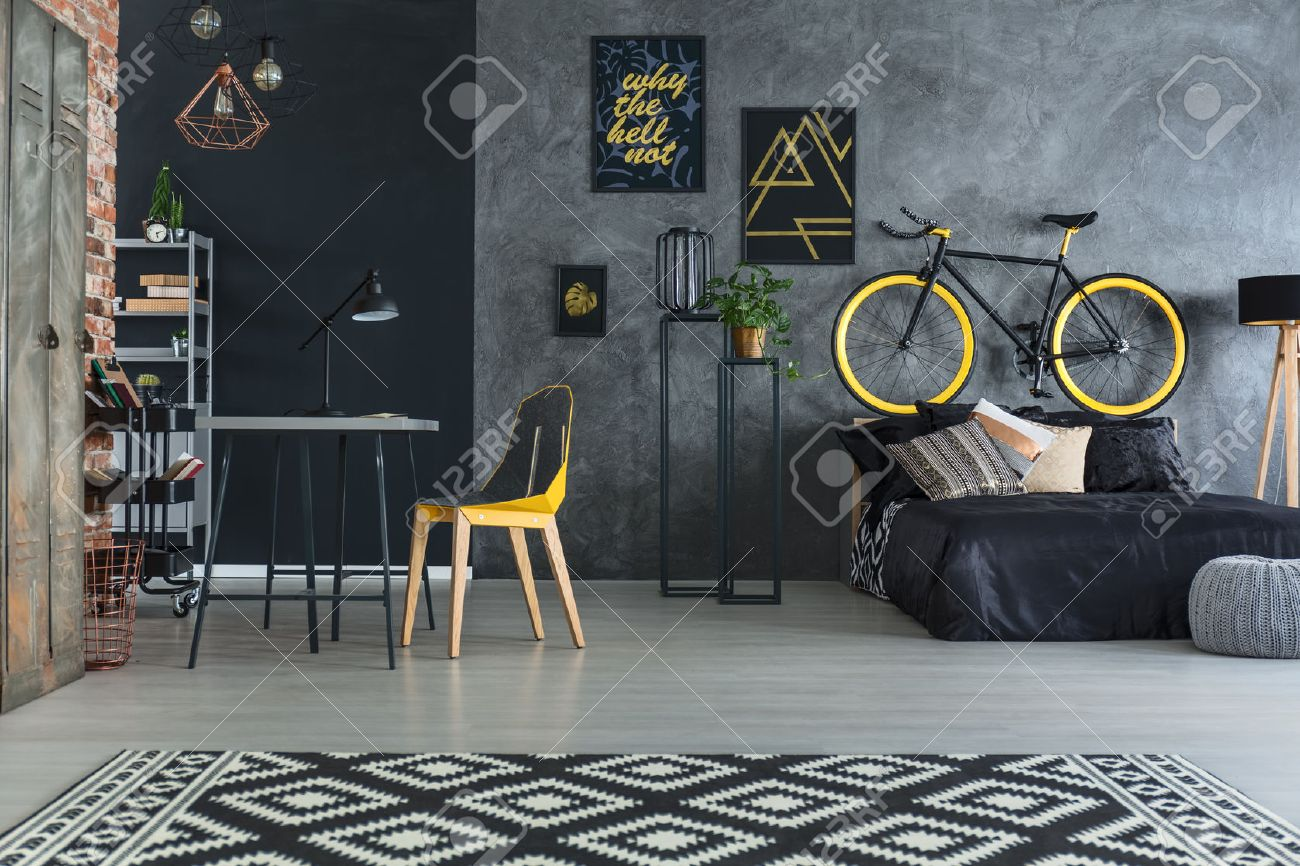 Plain wood table with hipster brick wall background stock photo - Hipster Bedroom With Bed Desk Chair And Brick Wall