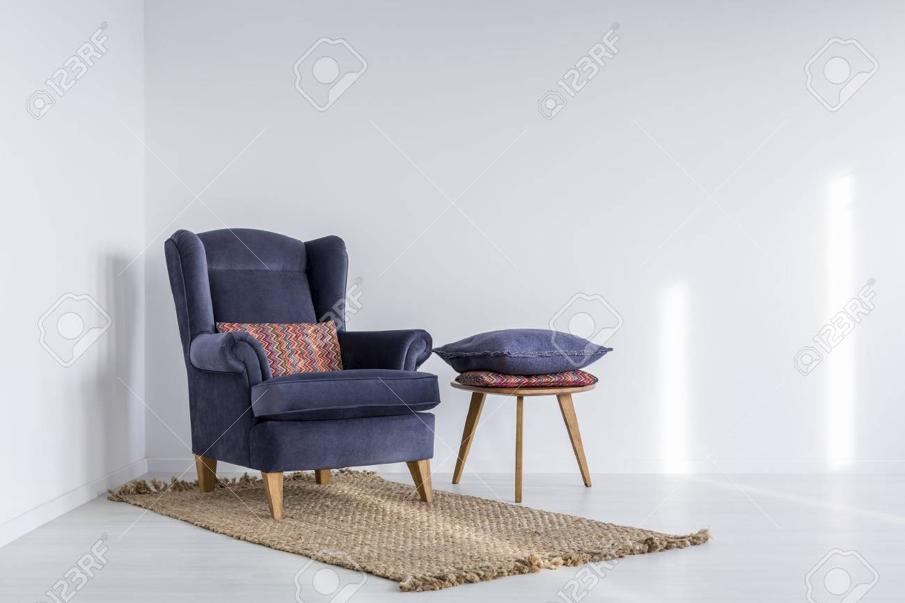 Stock Photo   White Interior With Navy Blue Armchair, Rug And Side Table