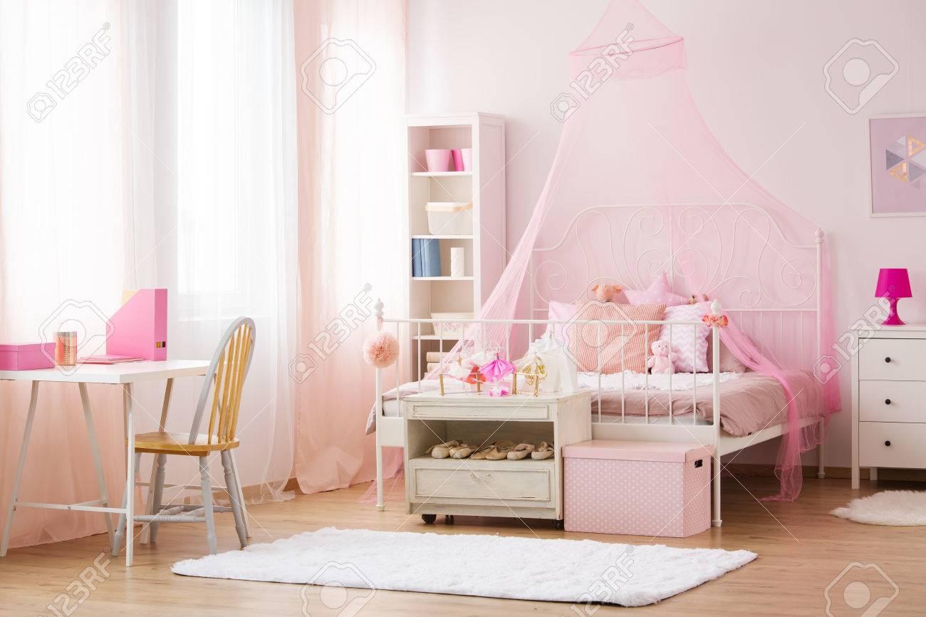 Chambre fille avec lit à baldaquin rose, bureau et chaise
