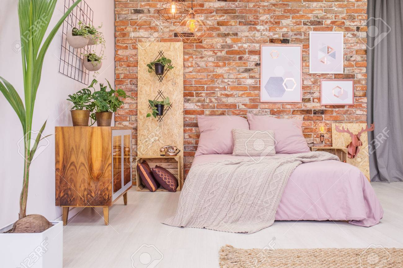 Bedroom with double bed, brick wall and green decorative plants Standard-Bild - 71353749