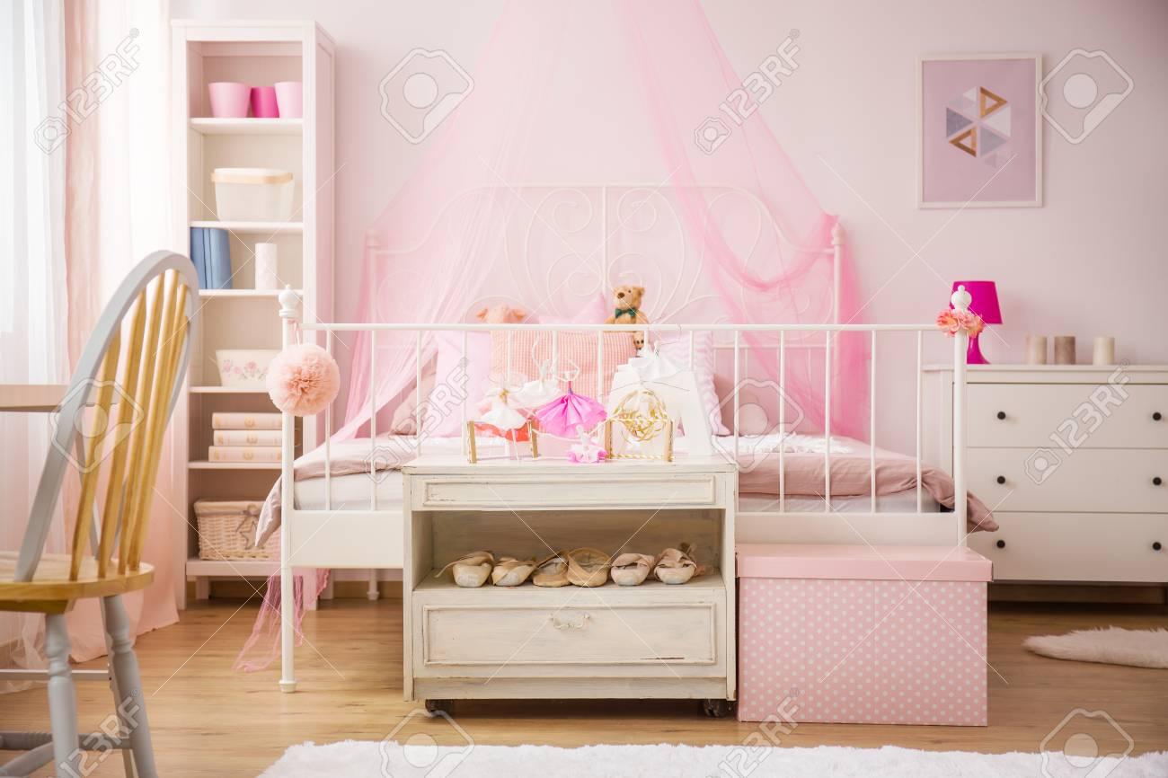 Chambre rose avec lit à baldaquin et mobilier blanc