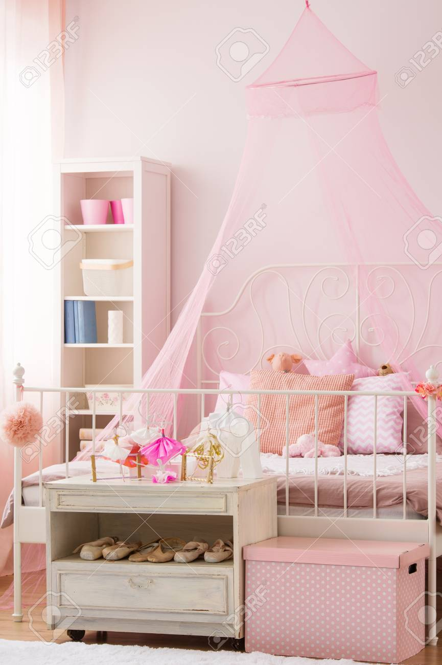 Pink Girls Bedroom With Canopy Bed And White Bookshelf Stock Photo