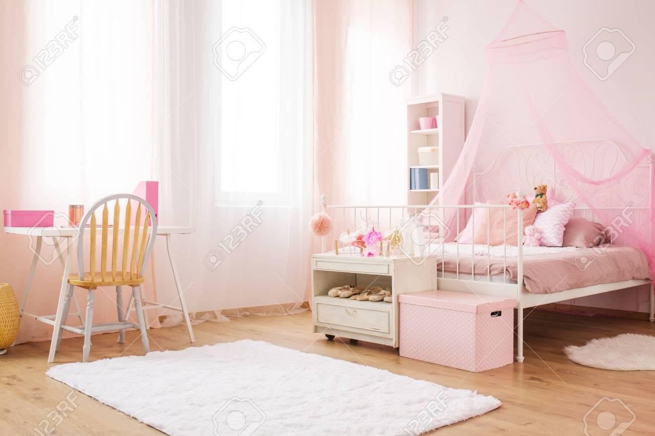 Petite chambre princesse rose avec lit à baldaquin, bureau et chaise