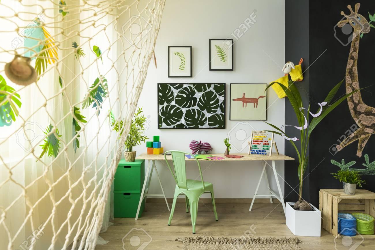 Les enfants étudient lespace avec le bureau la chaise verte et le