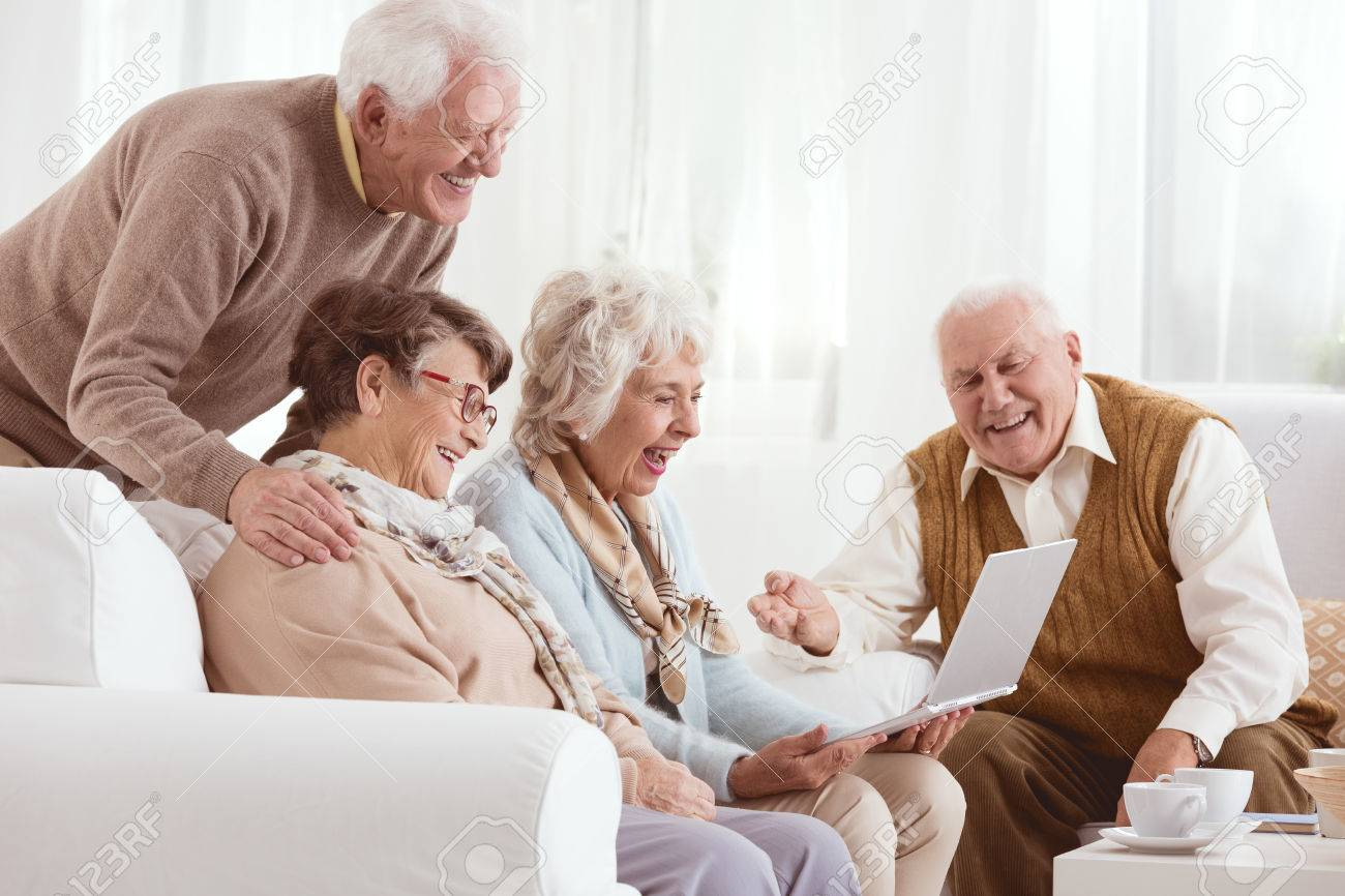 Senior friends watching old photos together on a laptop - 71490314