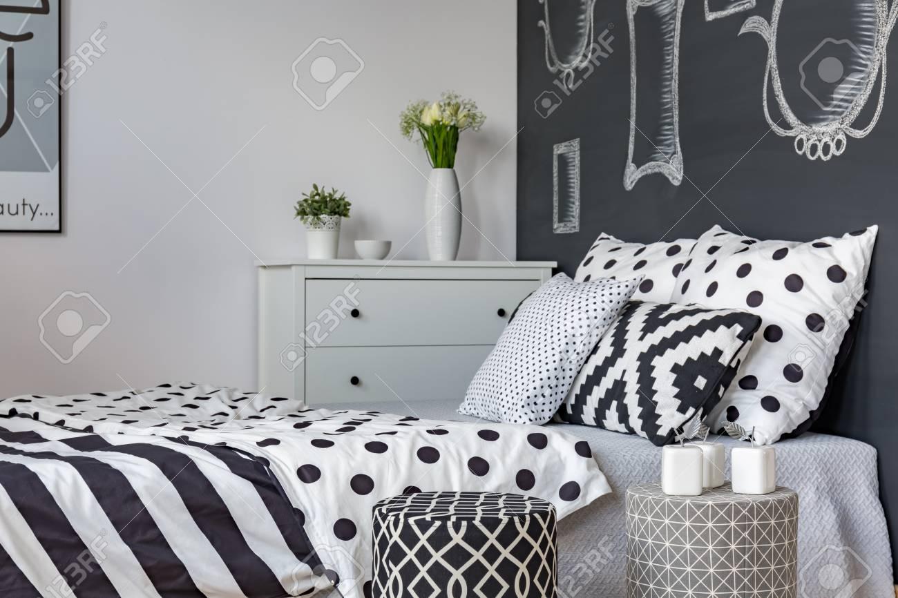 Lit noir et blanc dans la chambre à coucher avec mur de tableau
