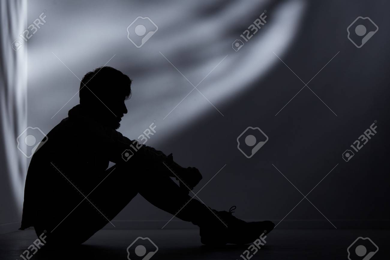 Abandoned man sitting on floor in dark room - 72322959
