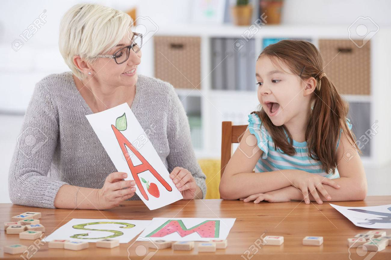 Girl with language disorder spelling letters with speech therapist - 72322922