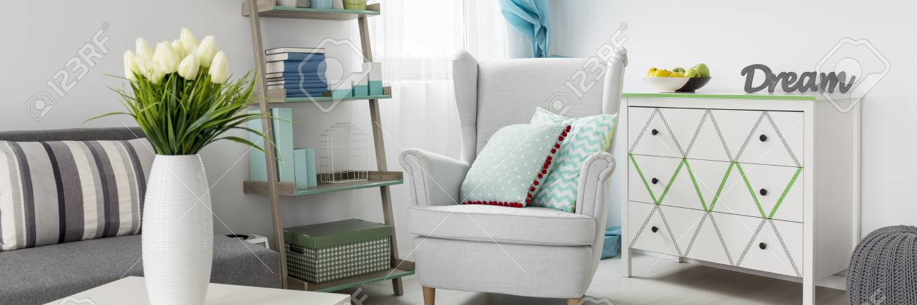 . Comfortable armchair in a cosy living room in light colours