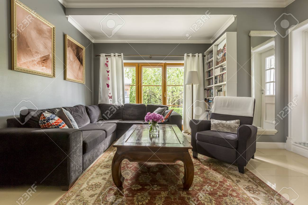 . Comfortable living room interior with gray corner sofa and classic