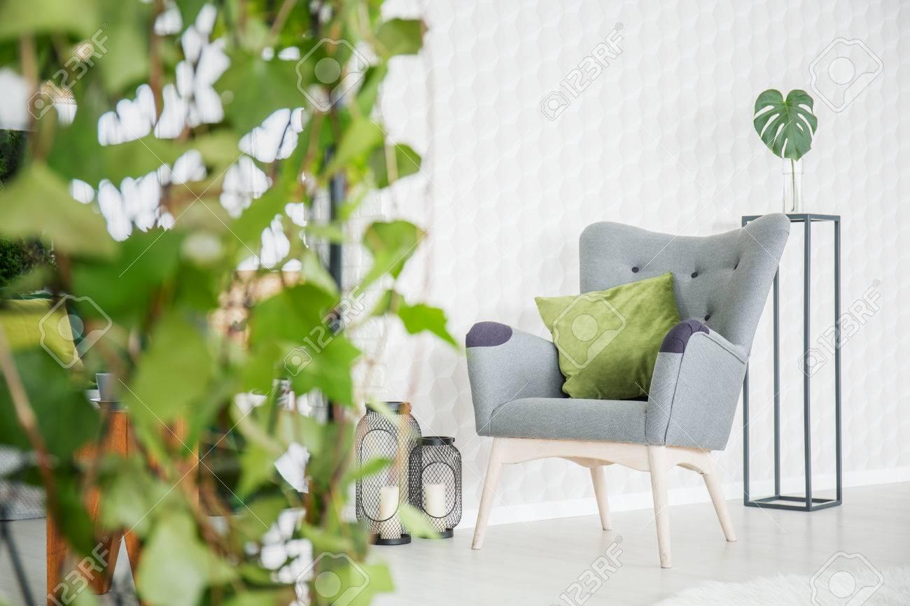 Chambre moderne blanche avec papier peint 3d, fauteuil et plante décorative