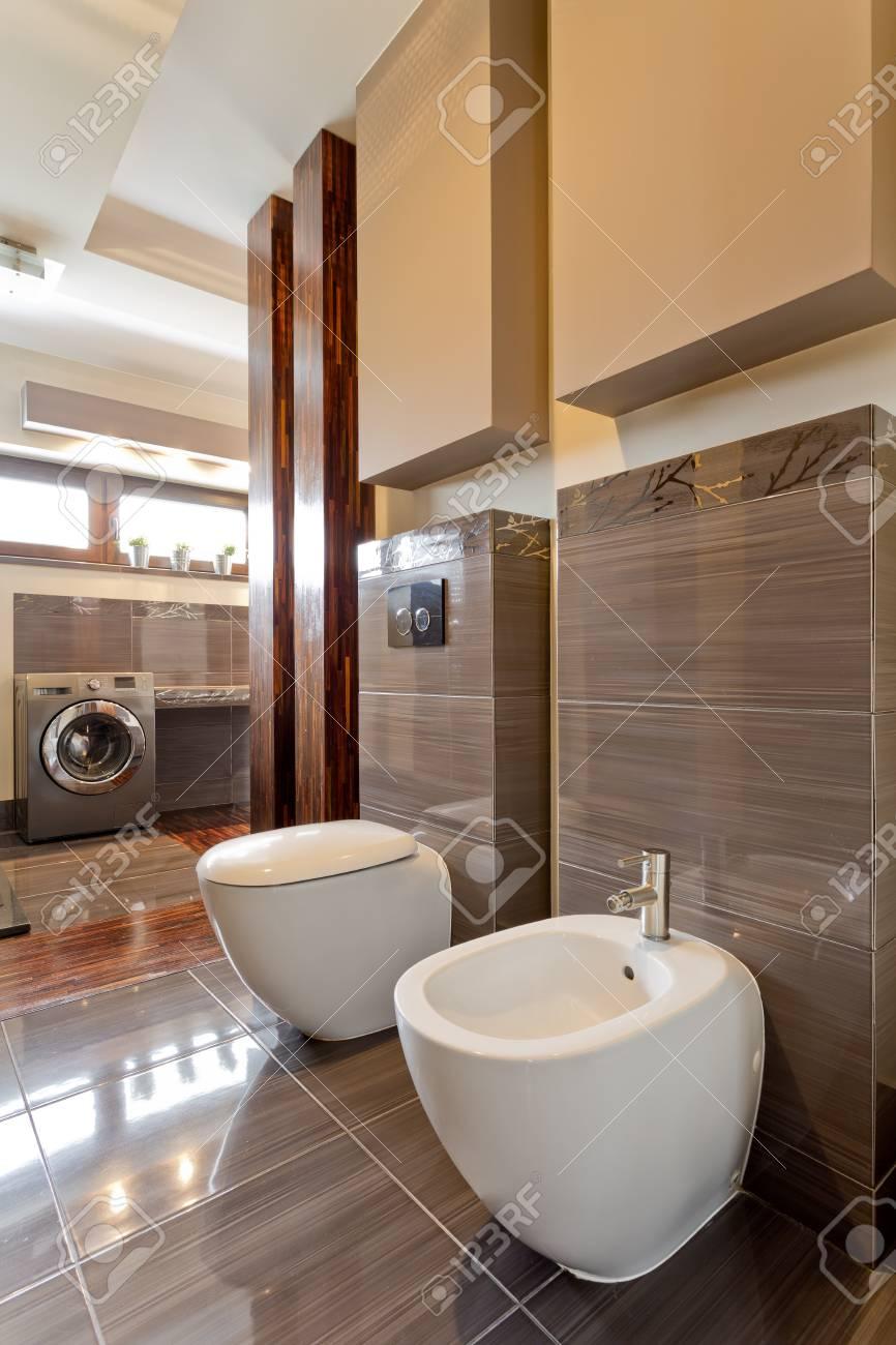 Geräumiges Badezimmer Mit Braunen Fliesen, Toilette, Urinal Und ...
