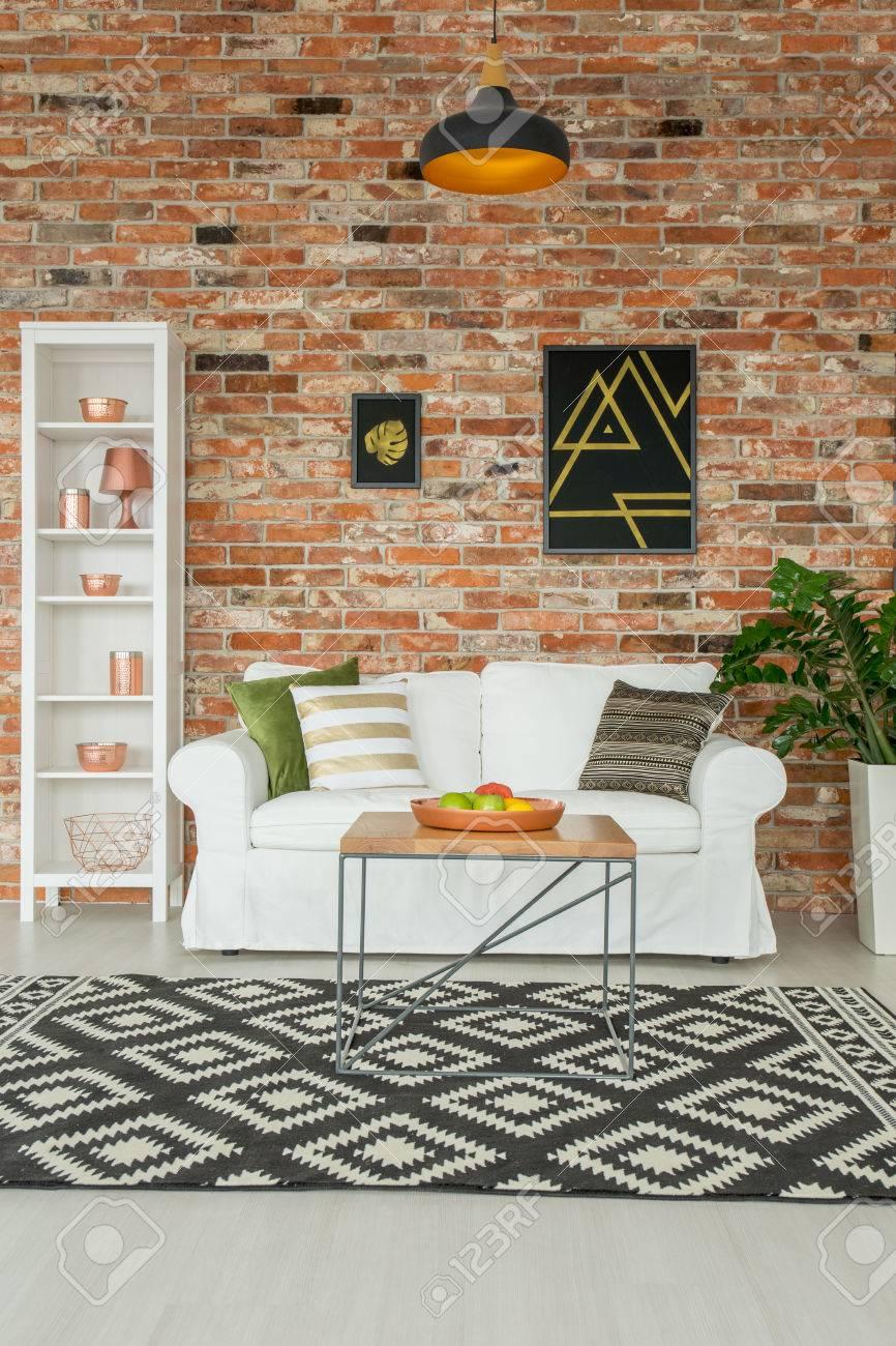 Salon moderne avec canapé blanc, bibliothèque et mur de briques