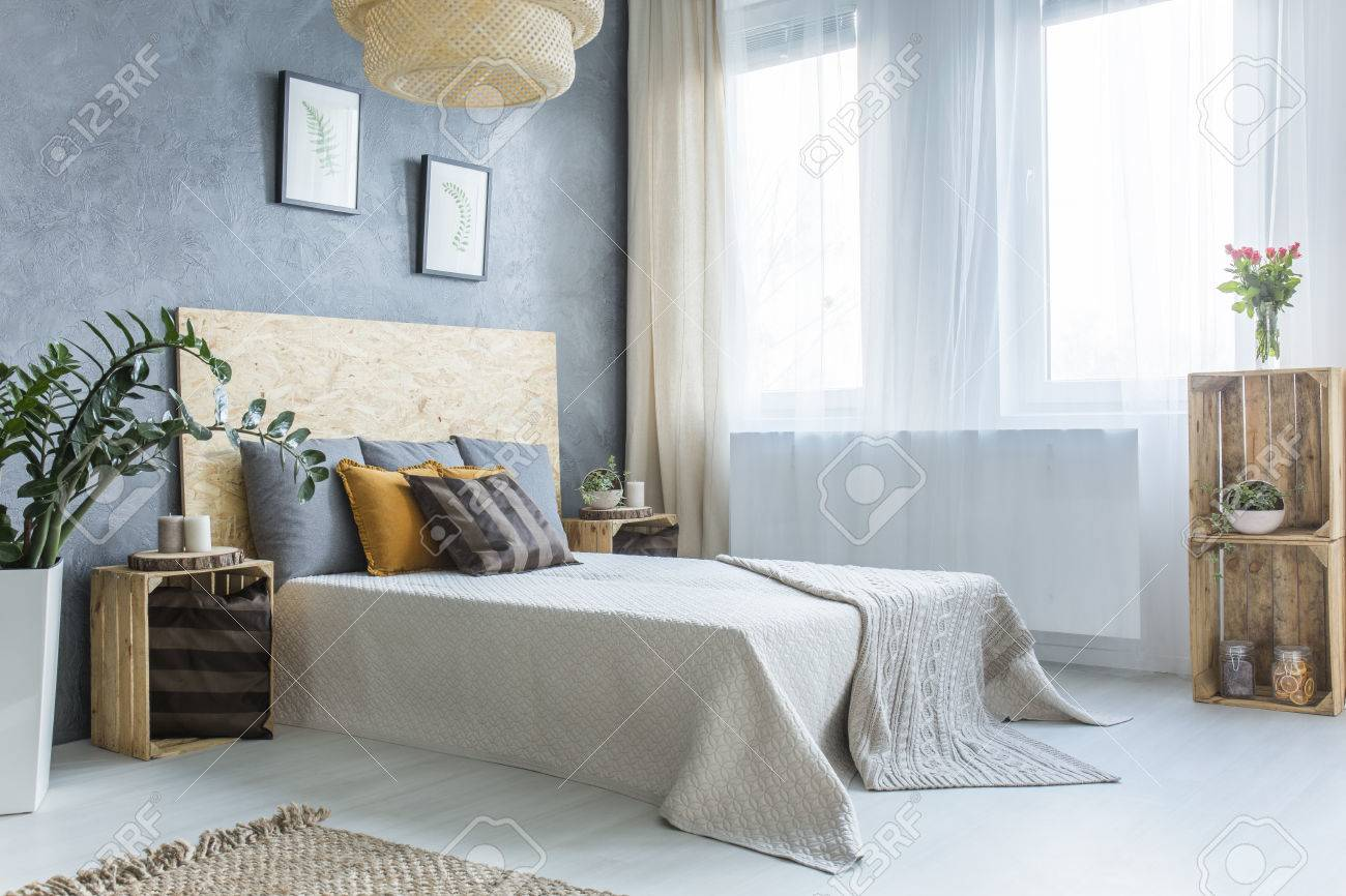 Graues Schlafzimmer Mit Kistenmöbeln, Doppelbett Und Pflanzen ...