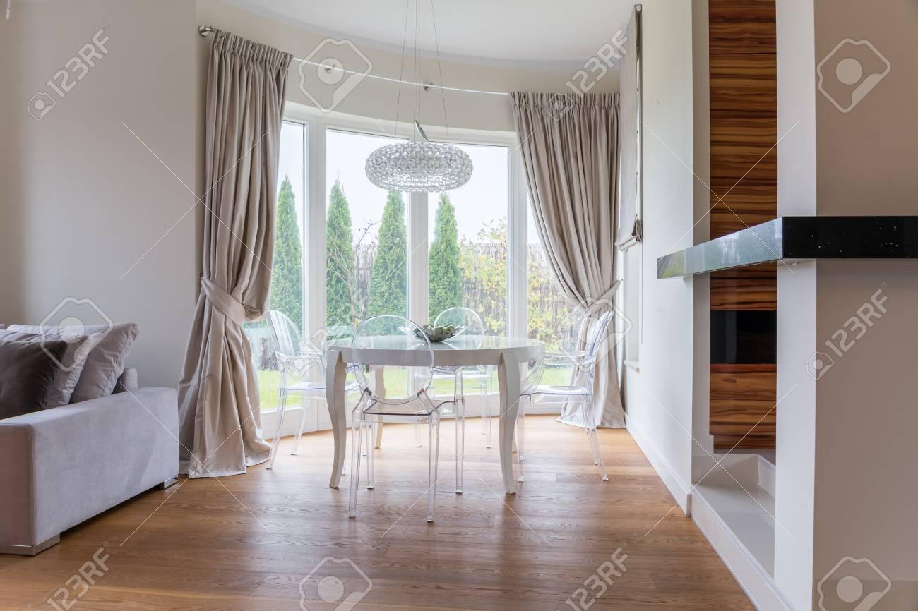 Elegante espacio de comedor con mesa blanca y sillas de vidrio