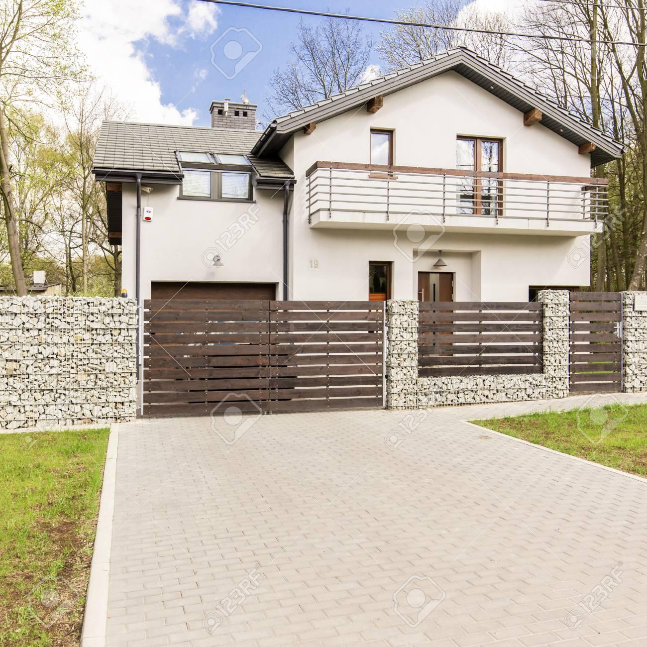 Maison individuelle blanche moderne avec une entrée et une clôture en bois