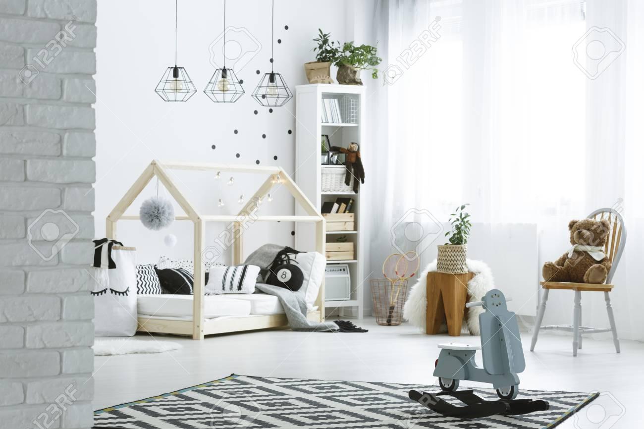 Chambre d\'enfant avec mur de briques, lit, lampes, jouets et bibliothèque