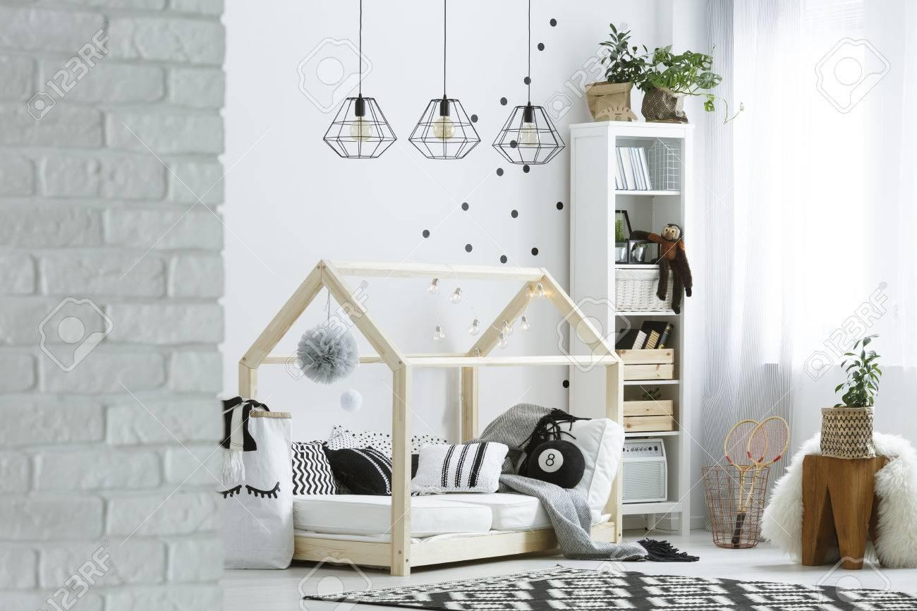 Chambre enfant avec mur de briques, lampes, lit et tapis de modèle