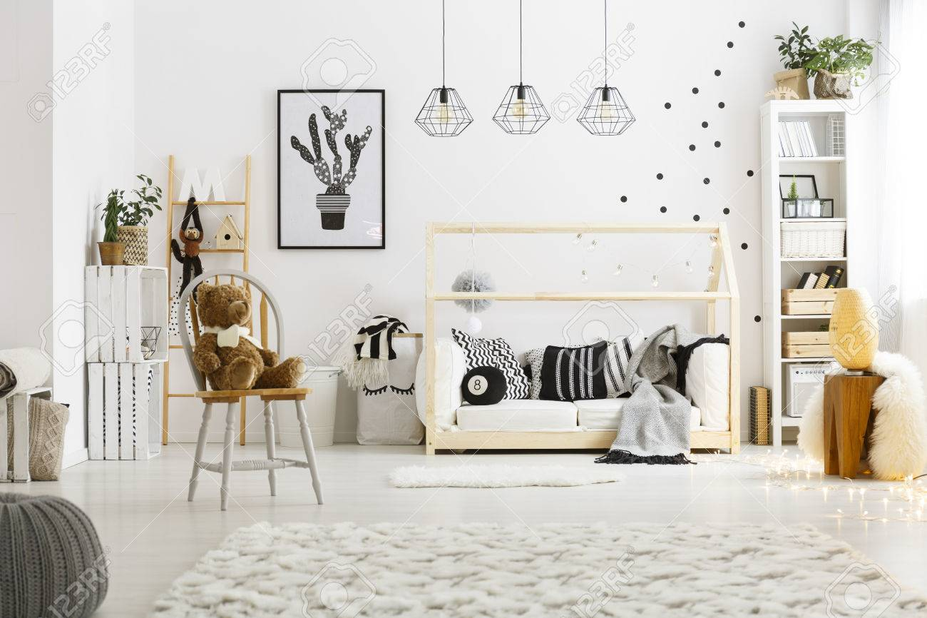 White child bedroom with carpet, pouf, chair, bed and bookcase Standard-Bild - 74570358